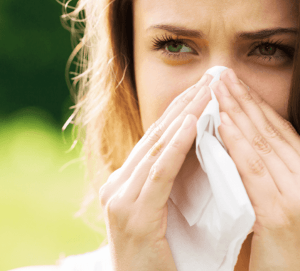 Person sneezing into tissue
