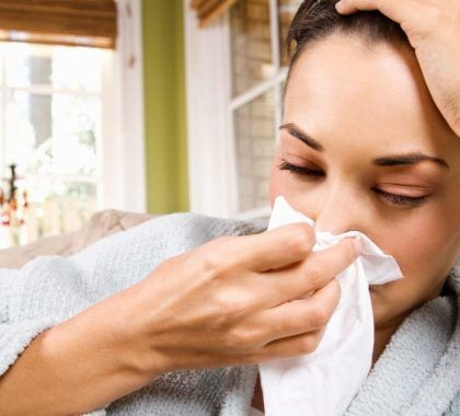 Person with cold rubbing nose with tissue