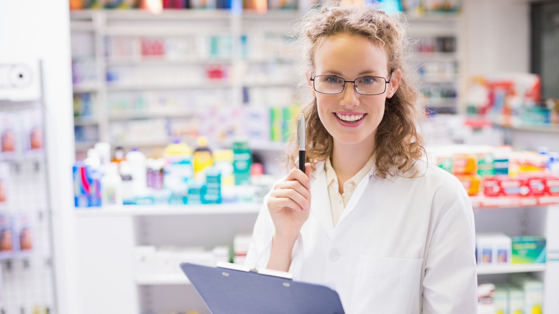 Smiling pharmacist with glasses and clipboard