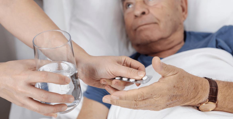 Carer handing medication to old man in bed