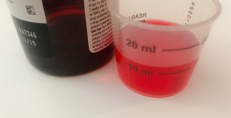 Red medicine in a measured beaker