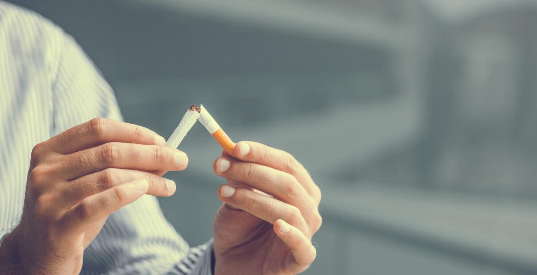 Someone breaking a cigarette in half