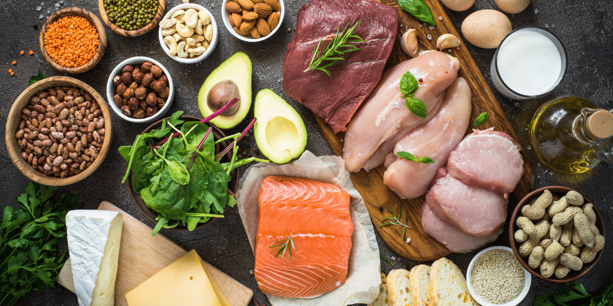 Variety of protein foods - salmon, meat, nuts, bread, avocado, cheese
