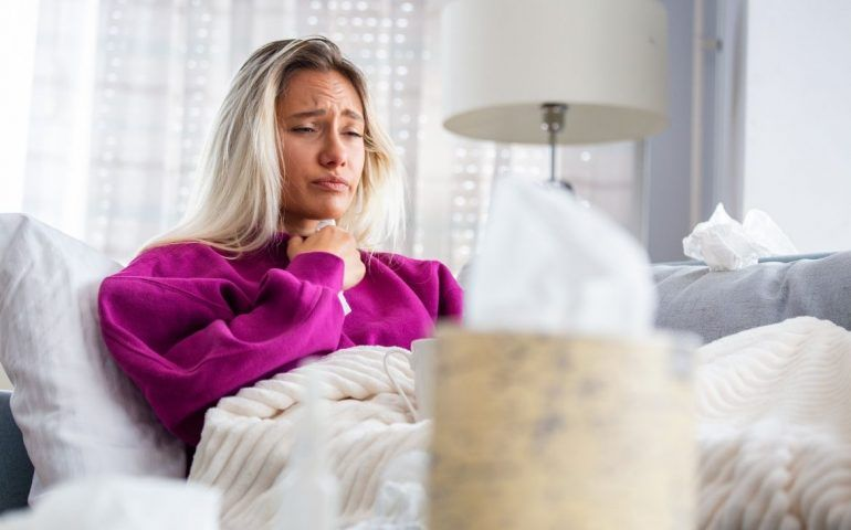 Person in bed clutching throat