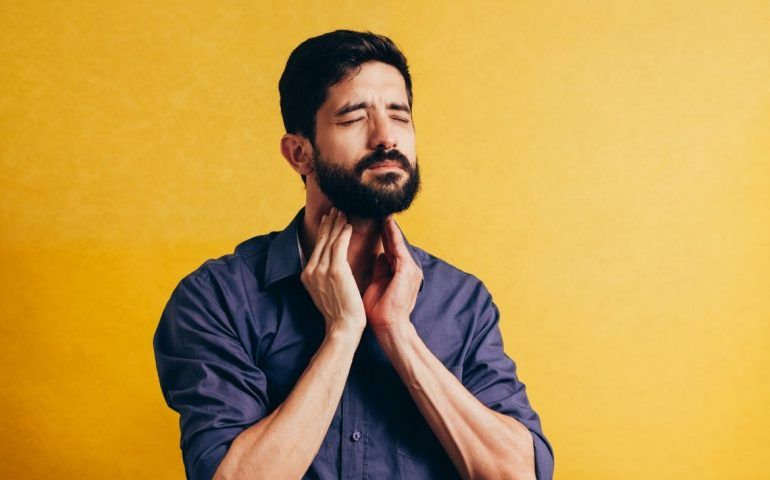 Frowning man clutching throat