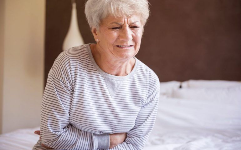 Old woman clutching bowels