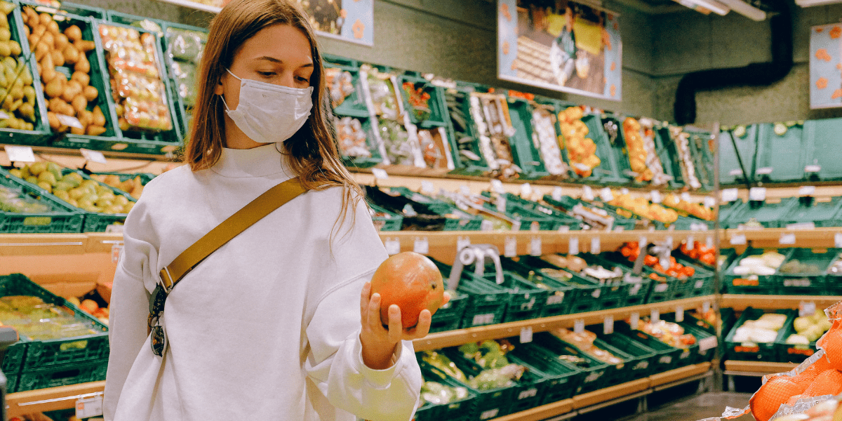 lady in the fruit aisle wearing a white mask