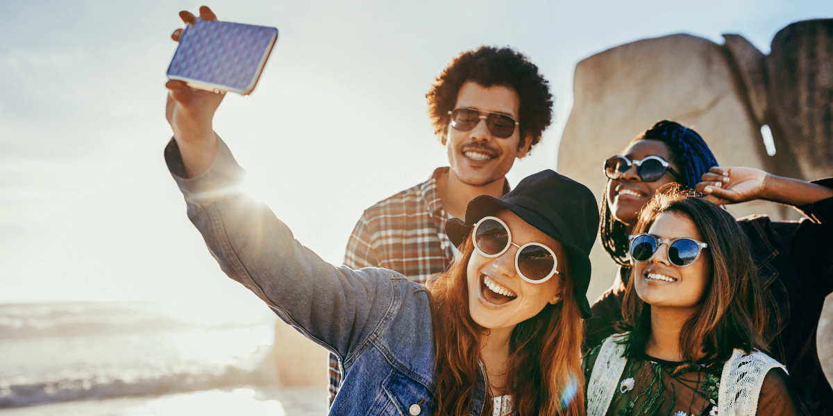 Group of friends taking a selfie on a sunny beach