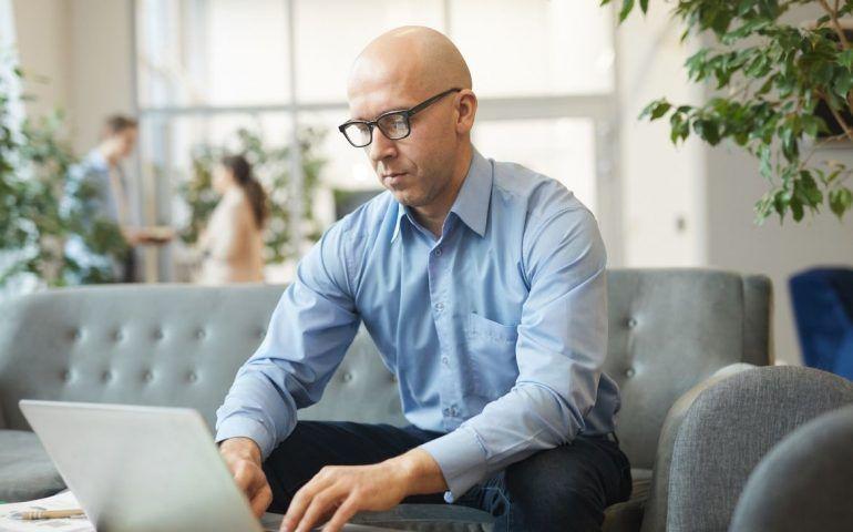 Bald man typing on laptop