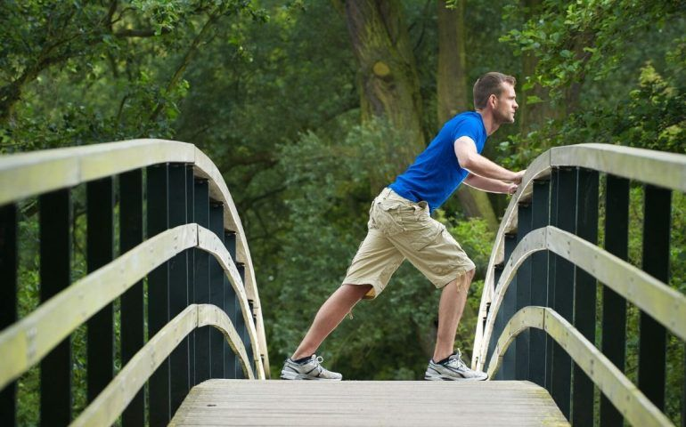 Person leaning on bridge outdoors