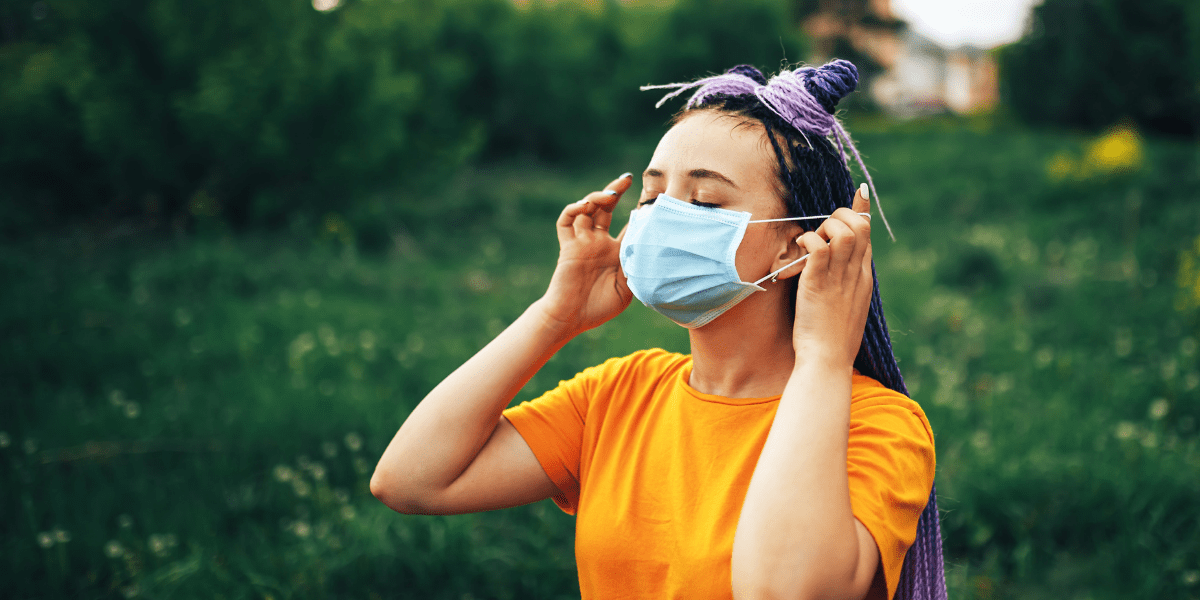 Person putting on face mask outdoors
