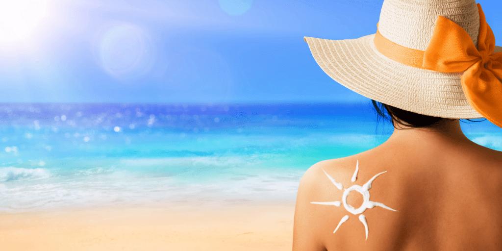 Woman with sun cream on shoulder on sunny beach